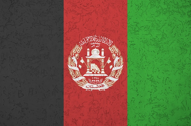 Afghanistan flag depicted in bright paint colors on old relief plastering wall. textured banner on rough background