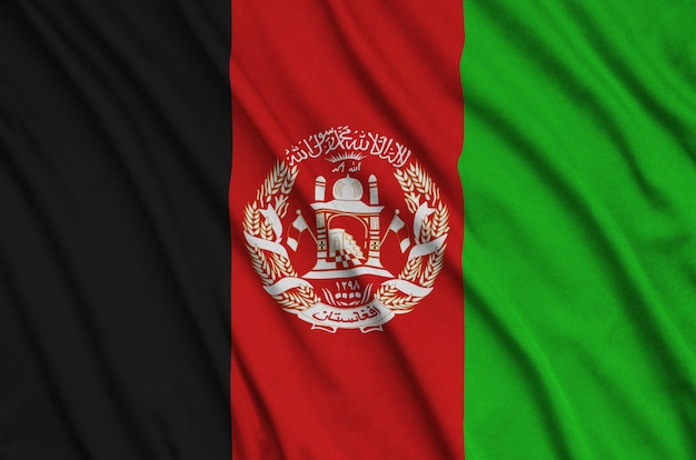 Afghanistan flag is depicted on a sports cloth fabric with many folds.