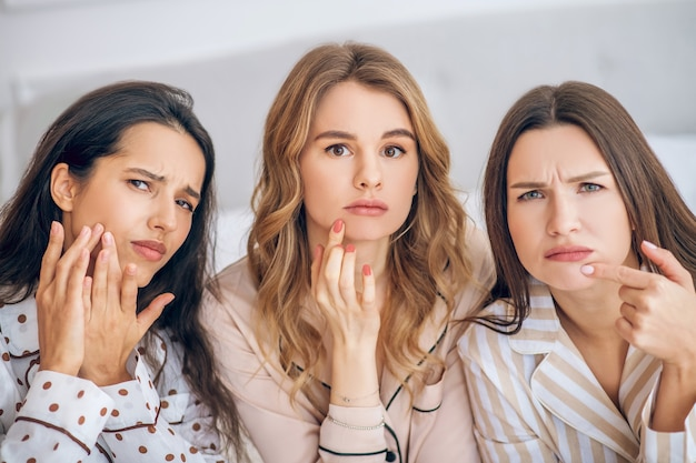 Afraid of aging. three girls touching their skin looking unsatisfied