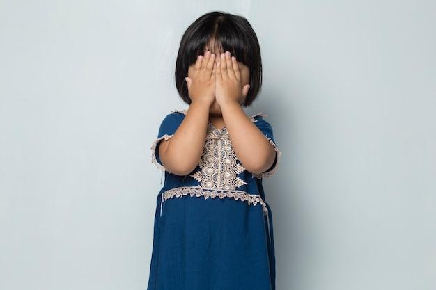 두려운 아시아 소녀는 흰색 배경에 손으로 얼굴을 가린다