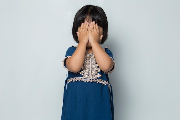 Afraid asian little girl covers her face with her hands on white background