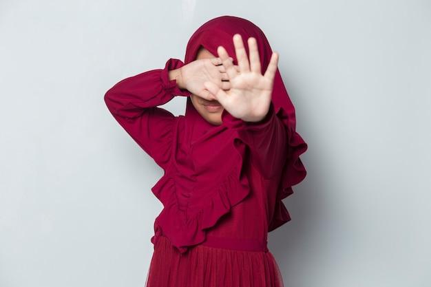두려운 아시아 이슬람 어린 소녀는 흰색 바탕에 손으로 얼굴을 가린다