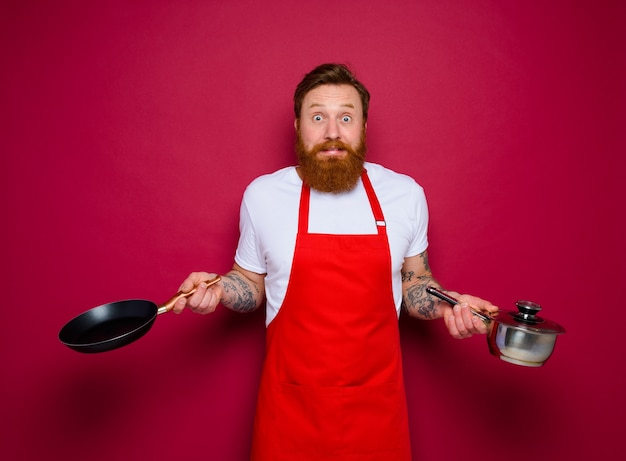 Afraid chef with beard and red apron cooks with pan and pot