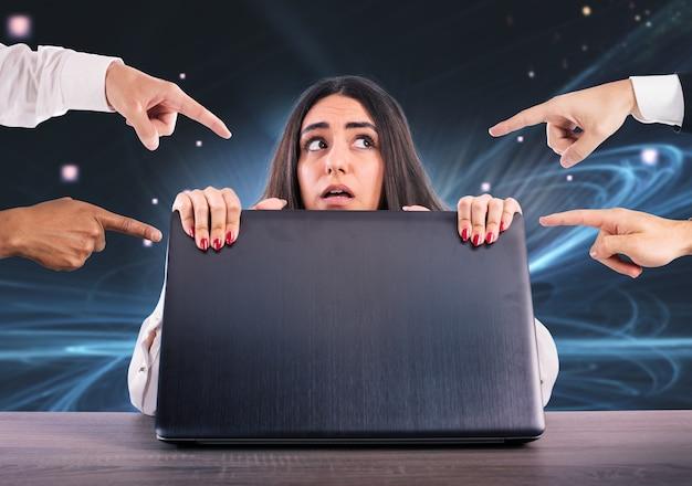 두려운 소녀가 노트북 뒤에 숨어 있습니다. 그녀는 사이버 괴롭힘의 피해자입니다