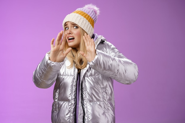 冬の帽子の銀のスタイリッシュなドレスで強烈な不快な若い金髪の女性が逃げるのを恐れて手を上げる自己防衛は頭を離れて怖がっている友人のこぼれ飲み物新しい服、紫色の背景。