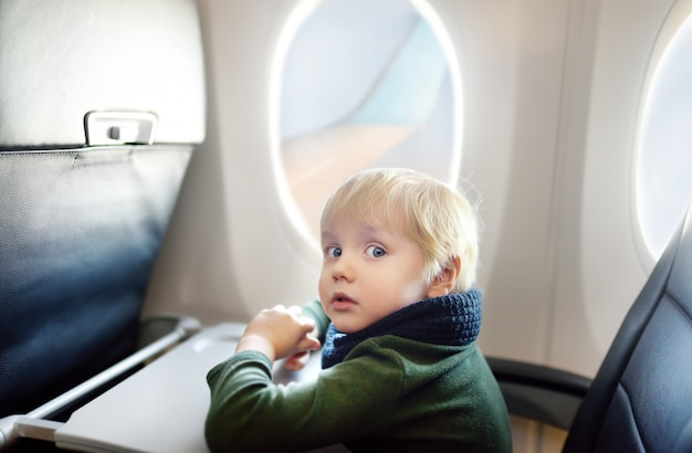 Afraid little boy sitting by aircraft window during the flight