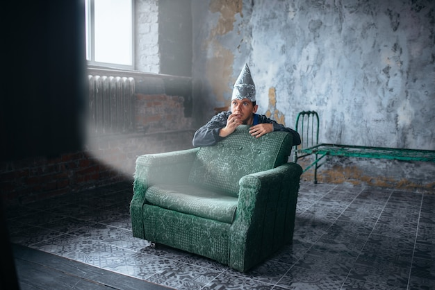 Afraid man in aluminum foil cap watch tv, mind protection, paranoia concept. ufo, conspiracy theory, telepathy phobia