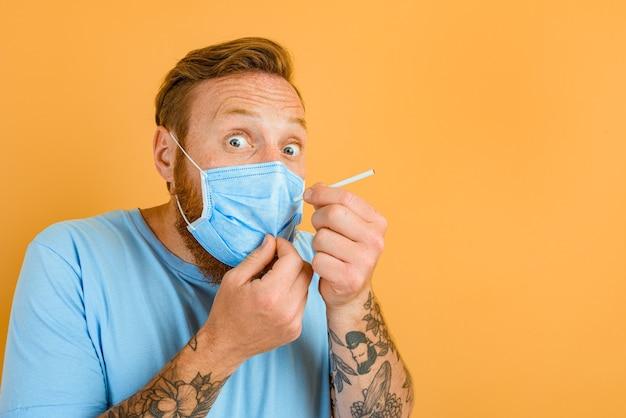 あごひげの入れ墨とcovidのマスクを持つ恐れている男はタバコを吸いたいです