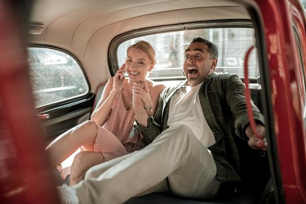속도를 두려워합니다. 빠른 차의 뒷좌석에 앉아 웃는 아내의 손을 잡고 겁 먹은 남자.