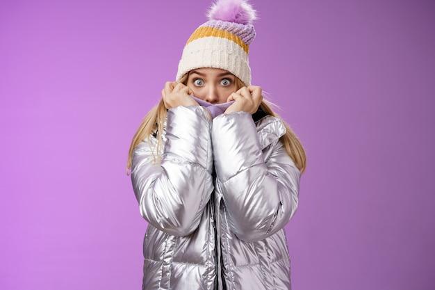 Испуганный шокированный молодой очаровательной сестры, потянув куртку, закрывающую лицо, пряча испуганный, страшный рассказ, снеговик, гуляющий по горам, широко раскрытыми глазами, обеспокоенный взглядом камеры страха, стоя на фиолетовом фоне.