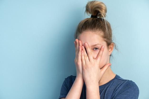 彼女の指を通して見る恐れている10代の少女