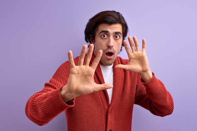 紫色の壁に隔離された手で身振りで停止する防衛態度の若い男を恐れて