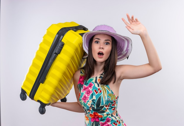 Afraid young traveler woman holding suitcase on isolated white wall