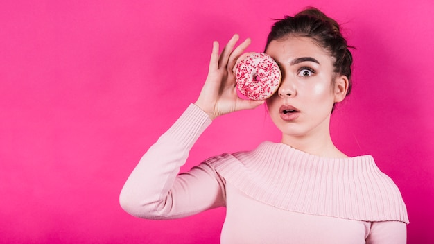 Afraid young woman holding donut over her eyes against pink backdrop