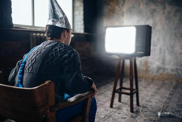 Напуганный человек в шлеме из алюминиевой фольги сидит в кресле