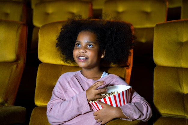 The africa girl is seating and watching the cinema at movie theater seats. the faces have feeling happy and enjoy.