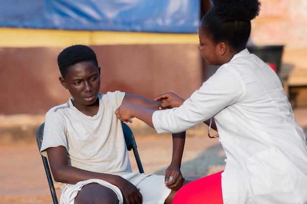 Medico dell'aiuto umanitario dell'africa che si prende cura del paziente