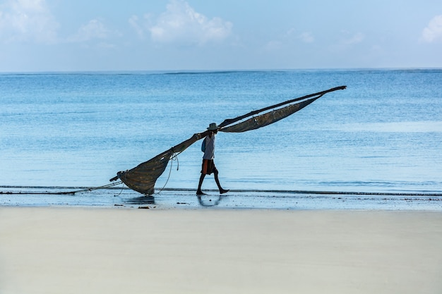 Africa mombasa fisherman walking on the beach with a sail for a boat,