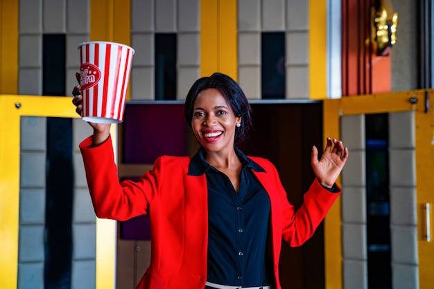The africa womand is standing and holding popcorn bucket at movie theater. the face has feeling happy and enjoy.
