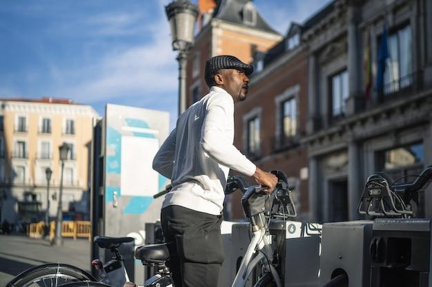 乗るために公共の自転車を取っているアフリカ系アフリカ人の男性