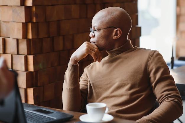 Афро-амейский предприниматель в рубашке с закатанными рукавами смотрит в окно с задумчивым и серьезным выражением лица, нервничает перед встречей с деловыми партнерами в кафе