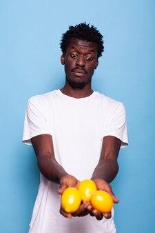 新鮮なレモンを保持し、ポーズをとるアフリカ系アメリカ人の大人