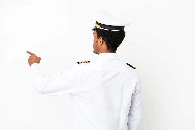 검지 손가락으로 가리키는 고립 된 흰색 배경 위에 아프리카 계 미국인 비행기 조종사