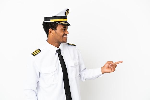 격리된 흰색 배경 위에 있는 아프리카계 미국인 비행기 조종사가 손가락을 옆으로 가리키고 제품을 제시합니다.