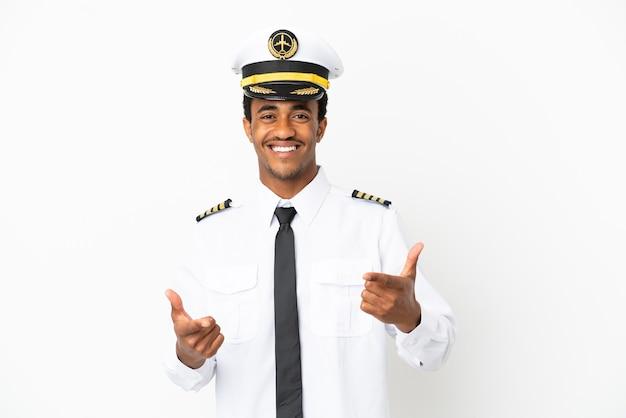 正面を指して笑っている孤立した白い背景の上のアフリカ系アメリカ人の飛行機のパイロット