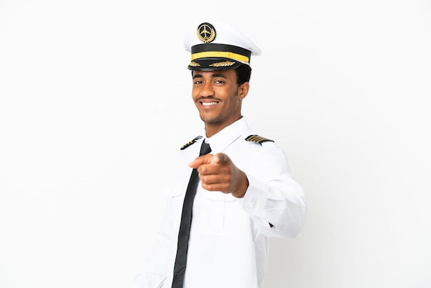 격리된 흰색 배경 위에 있는 아프리카계 미국인 비행기 조종사는 자신감 있는 표정으로 당신을 손가락으로 가리킵니다.