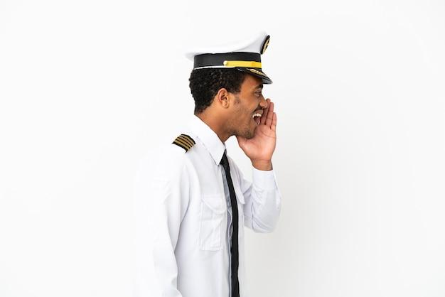 외진 흰색 배경 위에 있는 아프리카계 미국인 비행기 조종사가 입을 크게 벌리고 외쳤다