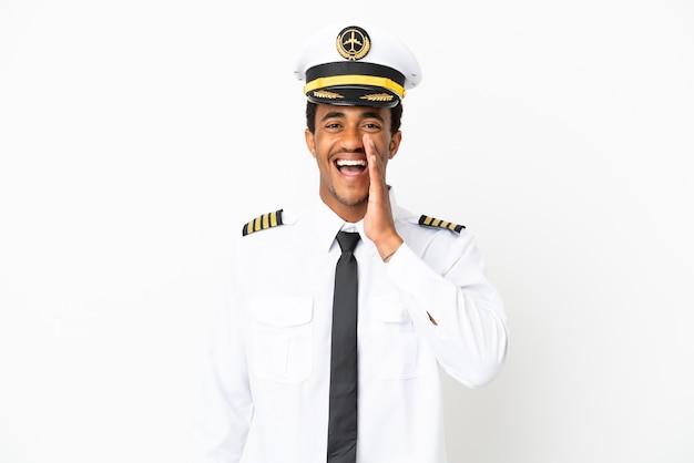 Афро-американский пилот самолета на изолированном белом фоне кричит с широко открытым ртом