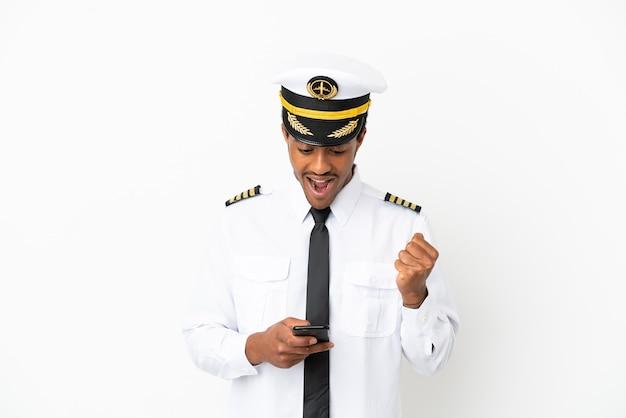 Афро-американский пилот самолета на изолированном белом фоне удивлен и отправляет сообщение
