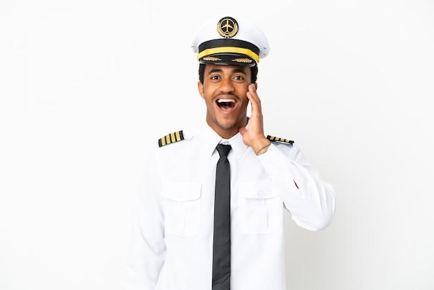 Афро-американский пилот самолета на изолированном белом фоне с удивленным и шокированным выражением лица