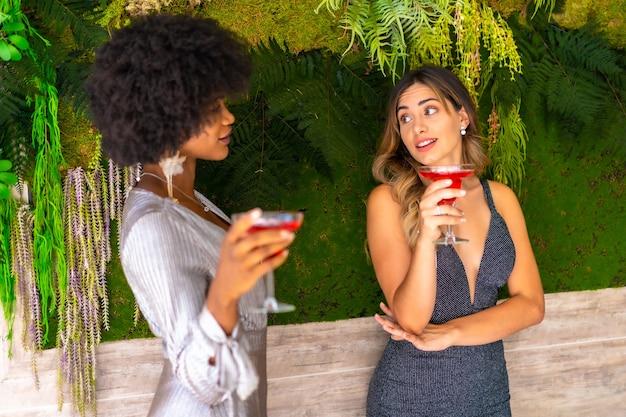 와인을 마시고 이야기하는 멋진 드레스를 입고 아프리카 계 미국인과 백인 여자 친구