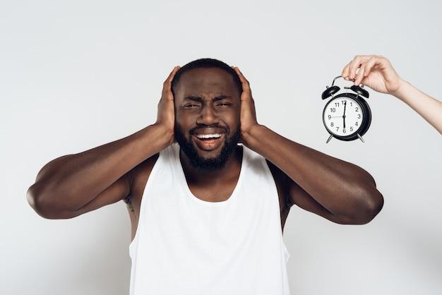 Афро-американский злой человек закрывает уши