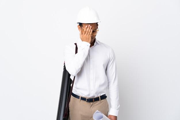 헬멧과 피곤하고 아픈 표정으로 격리 된 흰색에 청사진을 들고 아프리카 계 미국인 건축가 남자