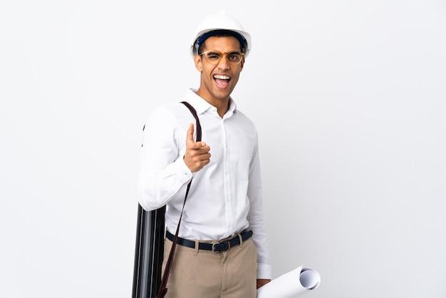 헬멧과 격리 된 흰색 배경 위에 청사진을 들고 아프리카 계 미국인 건축가 남자 _ 전면을 가리키고 웃