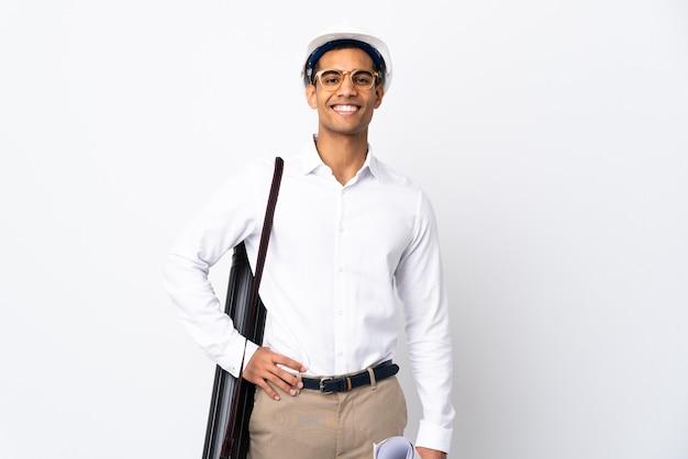 헬멧과 격리 된 흰색 배경 위에 청사진을 들고 아프리카 계 미국인 건축가 남자 엉덩이에 팔을 포즈와 미소