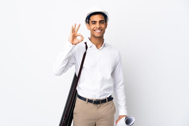 헬멧과 격리 된 흰색 배경 위에 청사진을 들고 아프리카 계 미국인 건축가 남자 손가락으로 확인 표시를 보여주는 _