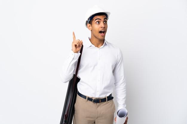 헬멧과 격리 된 흰 벽 위에 청사진을 들고 아프리카 계 미국인 건축가 남자 _ 손가락을 들어 올리는 동안 솔루션을 실현하려고