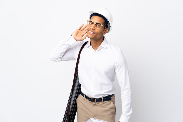 헬멧과 격리 된 흰 벽 위에 청사진을 들고 아프리카 계 미국인 건축가 남자 _ 귀에 손을 넣어 뭔가를 듣고
