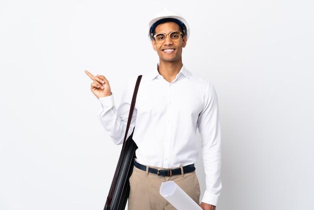 헬멧과 격리 된 흰 벽 _ 측면을 가리키는 손가락 위에 청사진을 들고 아프리카 계 미국인 건축가 남자