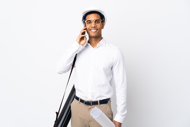 African american architect man with helmet and holding blueprints over isolated white wall _ keeping a conversation with the mobile phone with someone