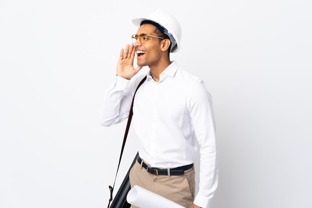 African american architect man with helmet and holding blueprints over isolated white wall _ shouting with mouth wide open to the side