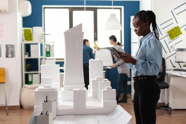 タブレットに取り組んでいるアフリカ系アメリカ人の建築家の女性