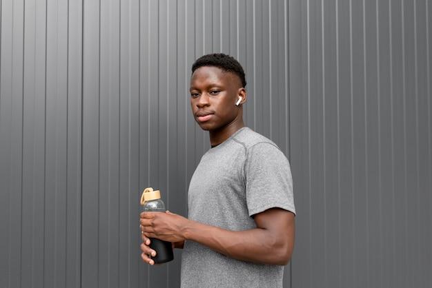 水のボトルを保持しているアフリカ系アメリカ人の運動選手