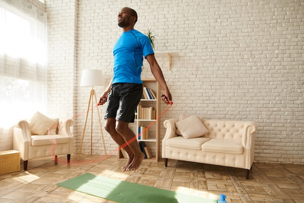 African american athlete jump with skipping rope at home.