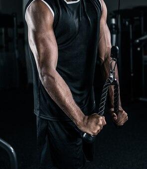 上腕三頭筋ロープでトレーニングするアフリカ系アメリカ人アスリート。