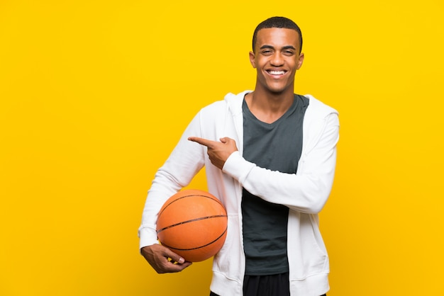 African american basketball player man pointing to the side to present a product